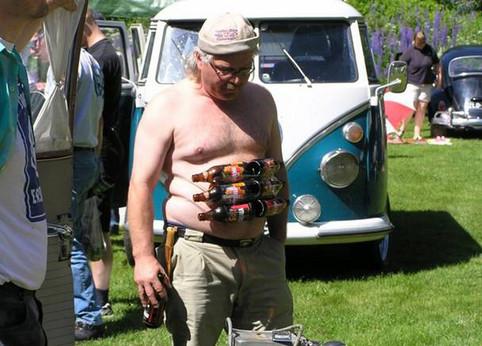 Ein alter Mann mit Bierflaschen als Sixpack vor seinem Bauch.